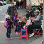 "Little girls playing ""Twinkle, Twinkle Little Stars,"" with a street performer."